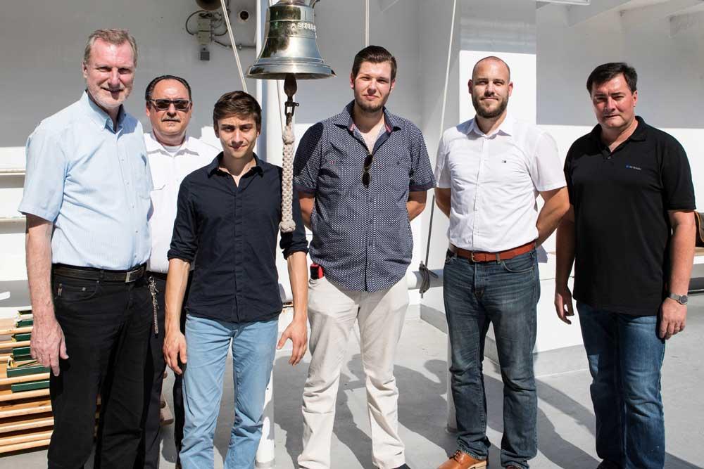 Klaus Paulus, Schulleiter des Schiffer-Berufskollegs Duisburg (l.), Volker Müßig, Leiter des Schulschiffs Rhein (2.v.l.), Oliver Kratky, Prüfungssachbearbeiter der IHK (2.v.r.) und André Stäudtner, Vorsitzender des IHK-Prüfungsausschusses (r.), gratulieren dem Klassenbesten Maximilian Scheliga (3.v.l.) und dem Prüfungsbesten Nino Mura (3.v.r.)