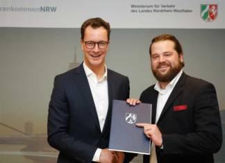 NRWs Verkehrsminister Wüst (l.) übergibt Christian Betchen von der KWS den Förderbescheid